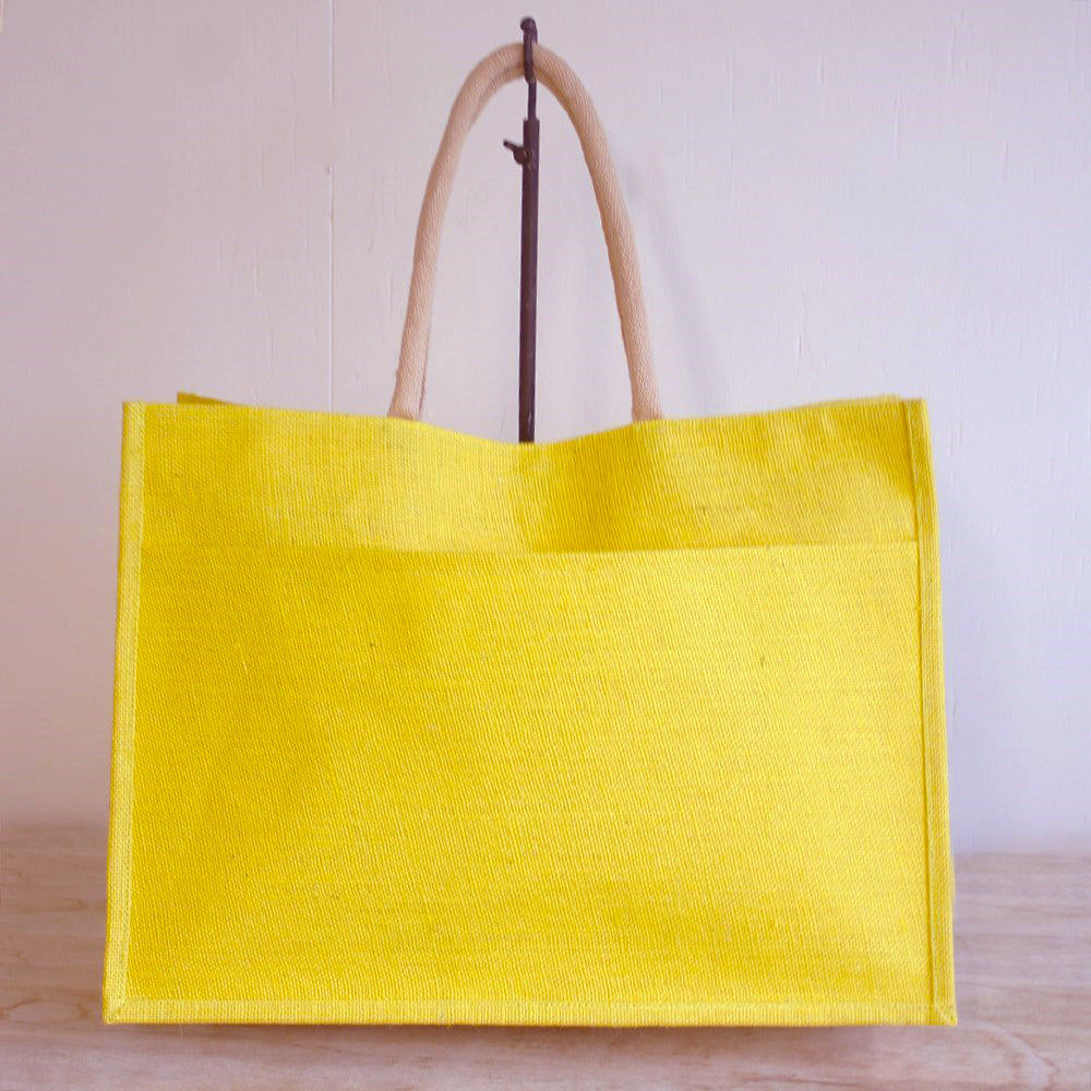 A lemon yellow jute tote with an outside pocket, suspended from a hook by its natural jute handles.