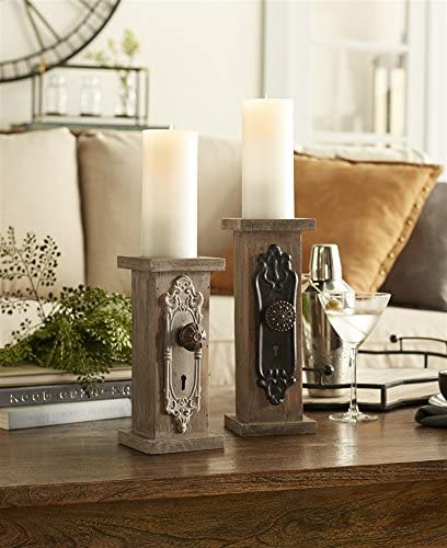 Two candle pedestals with door knob detailing on a table