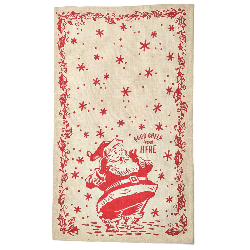 "Tan tea towel with red holly and berries border, snow falling and an illustration of Santa at the bottom.  Text next to Santa reads, ""Good Cheer Found Here"""