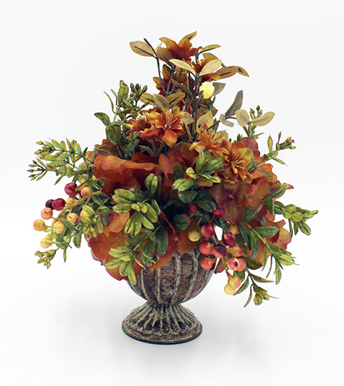 Fall floral arrangement with red and yellow berries in a mottled urn.