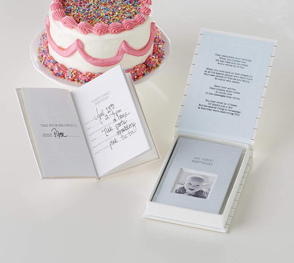 Table with a birthday cake and a guest book for baby opened to an entry page, and a guest book for baby displayed in an open gift box