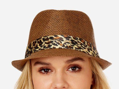 Model wearing a brown fedora with a satin leopard print band.