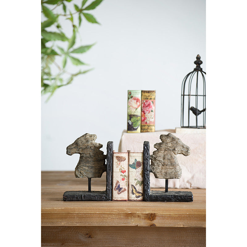 Rustic horse themed bookends.  Horses and supports appear to be carved.  Horses are tan and supports are dark brown.  Bookends are positioned on a table with floral themed books in between.