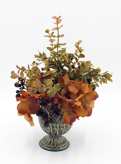 Floral arrangement with dark red berries in a patina urn.