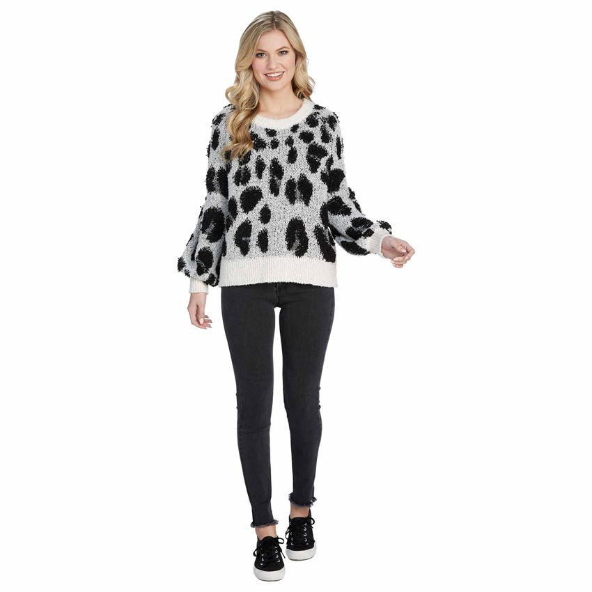 Model wearing leopard boucle sweater.  White sweater with black and brown spots.