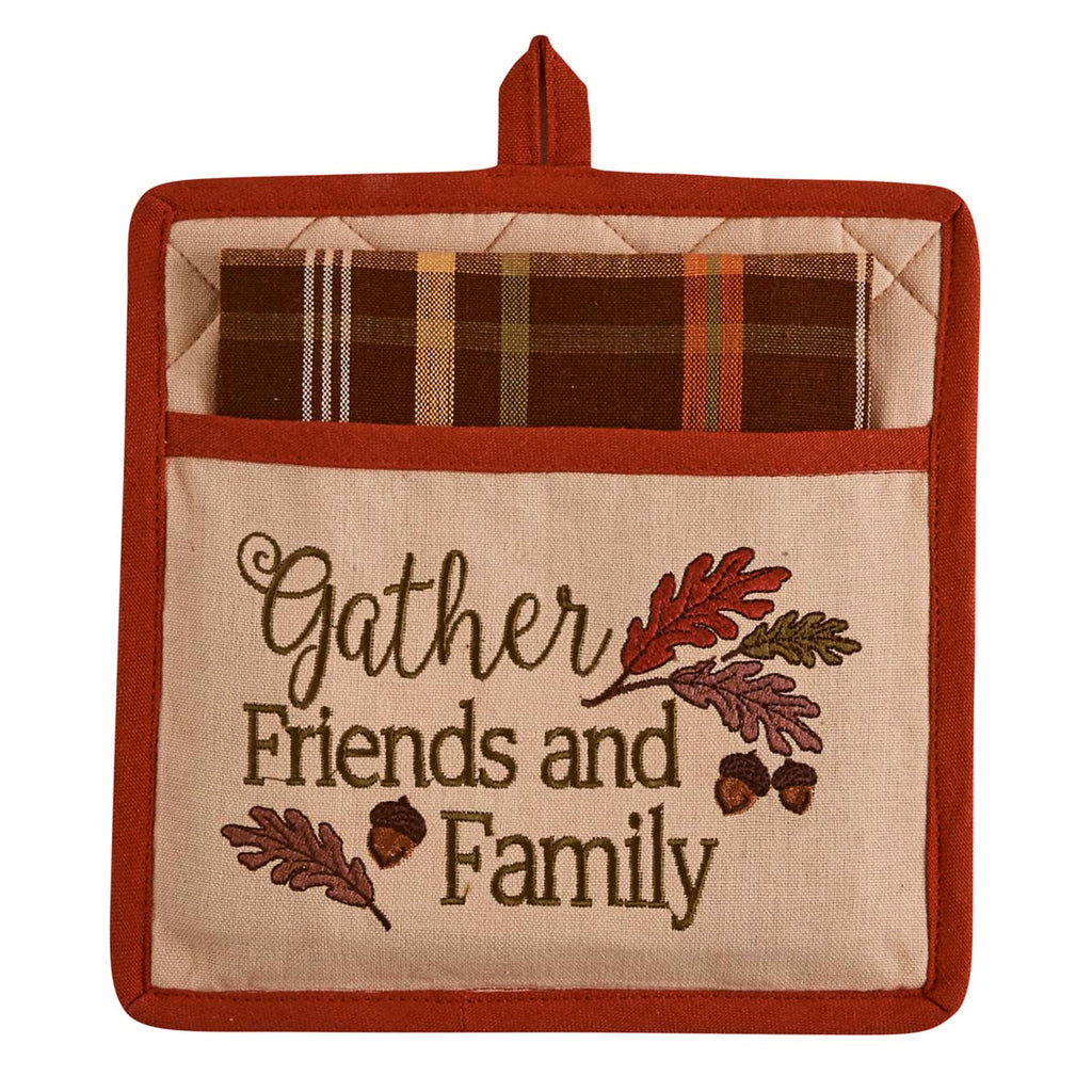 Embroidered potholder with the words 'gather friends and family' and several leaves and acorns.  Plaid dishtowel is folded within the opening of the potholder.