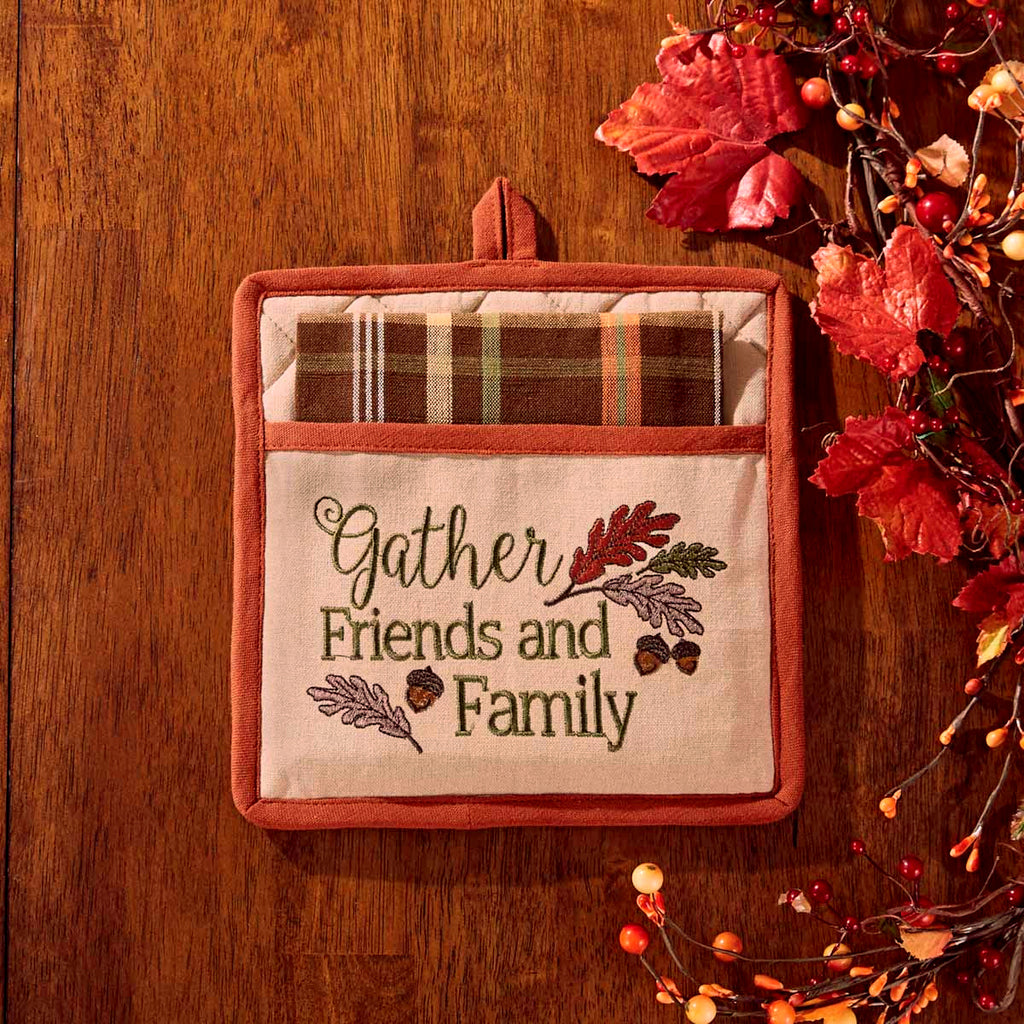 Embroidered potholder with the words 'gather friends and family' and several leaves and acorns.  Plaid dishtowel is folded within the opening of the potholder.  Potholder is on a wooden background with fall leaves and berries to the right.
