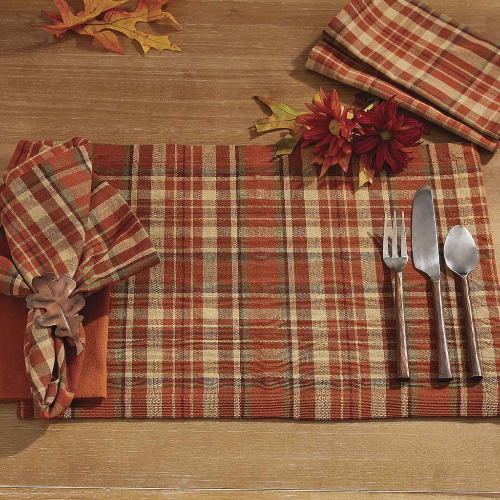 Place setting on a wooden table with a folded napkin in a leaf napkin ring, and copper finished silverware on top of a plaid placemat with orange, tan, green and burgundy colors.