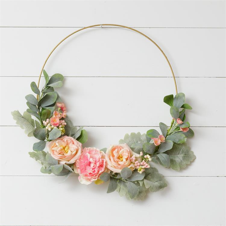 A gold hoop wreath hung on a white wooden slat wall.  The wreath features peach roses and other small pink blossoms around mint green leaves.  All of the flowers are collected at the bottom of the wreath and the upper portion of the hoop is bare.
