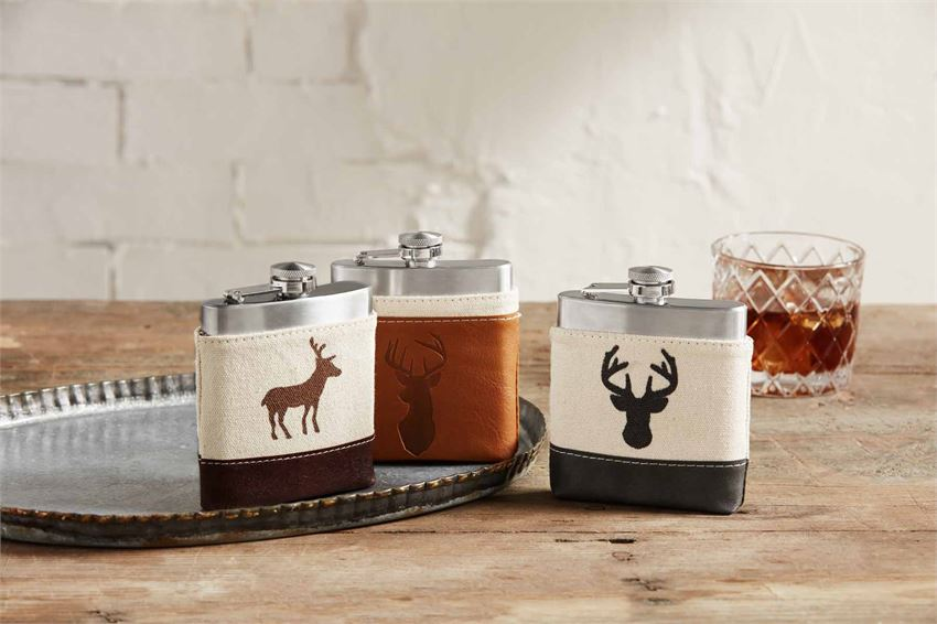 Collection of three flasks resting on a silver serving tray on top of a wooden table.  A rocks glass of whiskey is in the background.  Each stainless steel flask is in a canvas and fake leather pouch with an image of a deer.