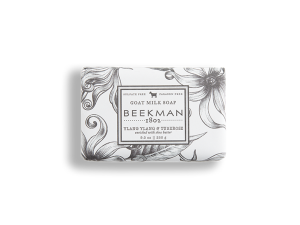 A 9 oz. bar of Ylang Ylang and Tuberose Goat Milk Soap in black and white floral packaging