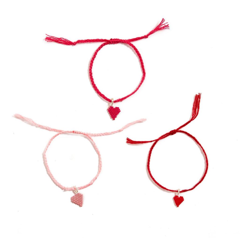 Three bracelets with cotton string and glass bead charm hearts.  One is hot pink, one light pink, and one red.