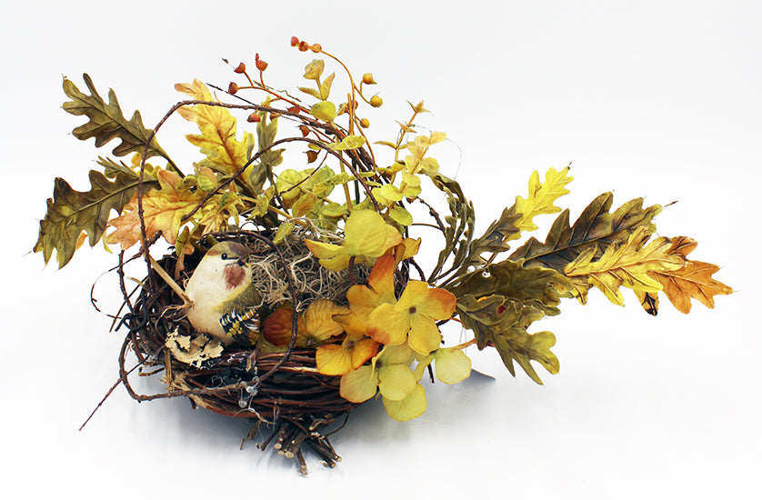 Birds nest with fake bird perched on rim.  Leaves twigs and berries radiate out from the nest.