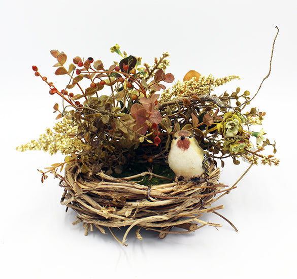 Round birds nest with fake bird on rim.  Floral arrangement is attached to the back of the nest to form a small canopy over it.