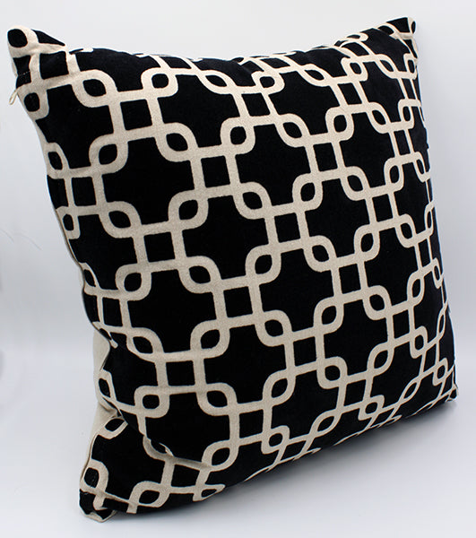 Tan pillow with raised black velveteen pattern creating interlocking squares across the front.