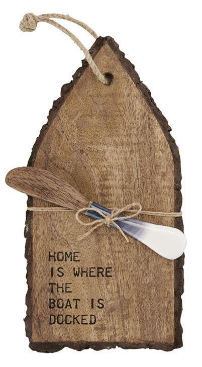 Mini serving board shaped like a boat from above.  Features a spreader tied to the board with twine.  'Home is where the boat is docked' is burnished in to the surface of the board.