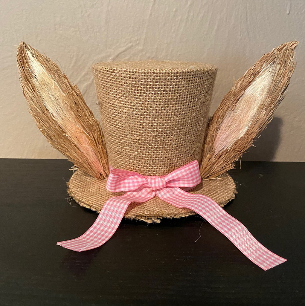 A burlap top hat with a ribbon of pink gingham tied in a bow, and features a pair of straw ears on either side.