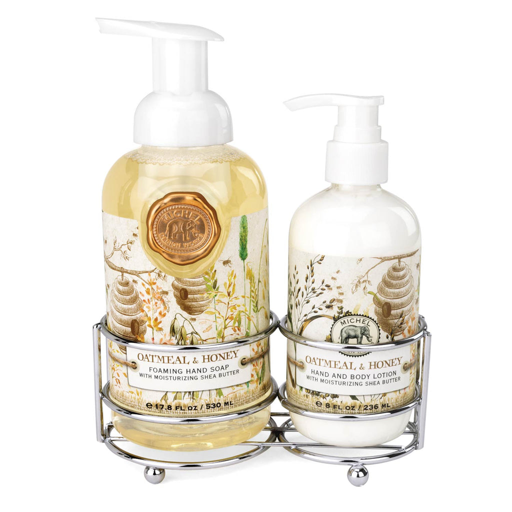 Soap and lotion set in a shiny silver metal caddy.  The label of each bottle features bee hives, wheat and trees.  The hand soap has a bronzed wax stamp with Michel Designs logo embossed.