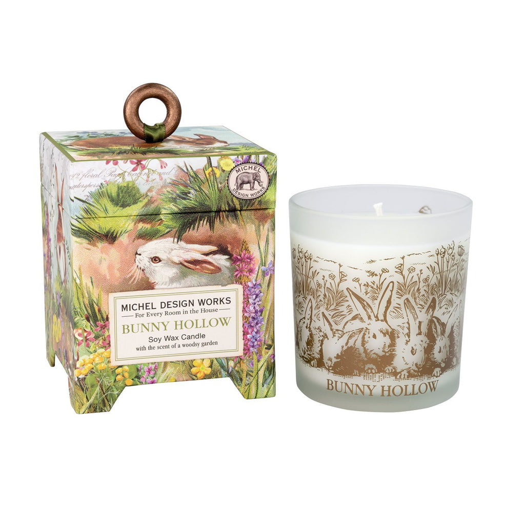A gift box with a printed design of frolicking bunnies in a hollow surrounded by spring flowers next to a candle in a frosted glass vessel.  On the outside of the vessel is a brown line art design of a group of bunnies in a hollow and text below reads 'bunny hollow'