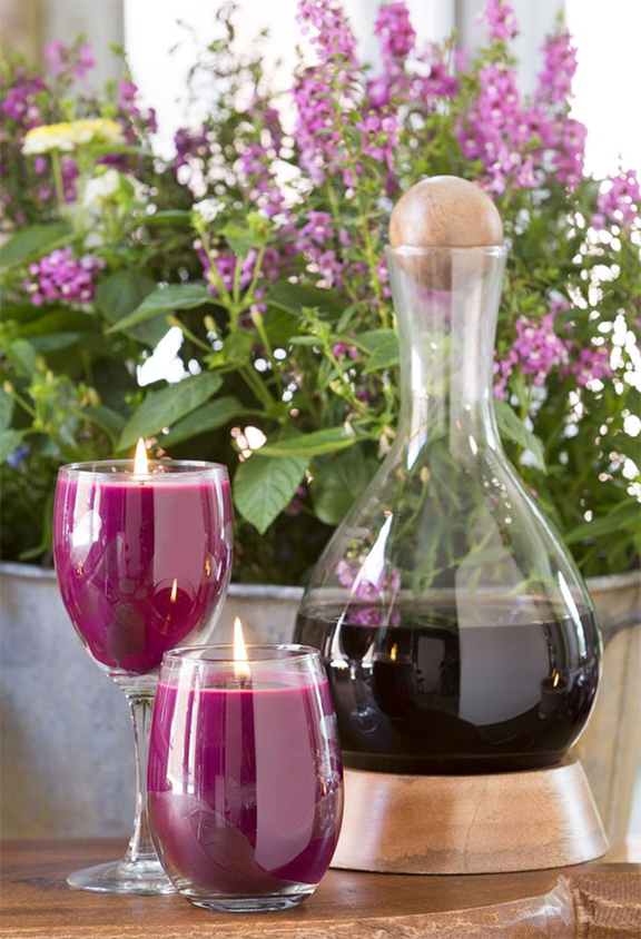 Stemless and stemmed wine glass candles next to a decanter of red wine in front of a planter of purple flowers.