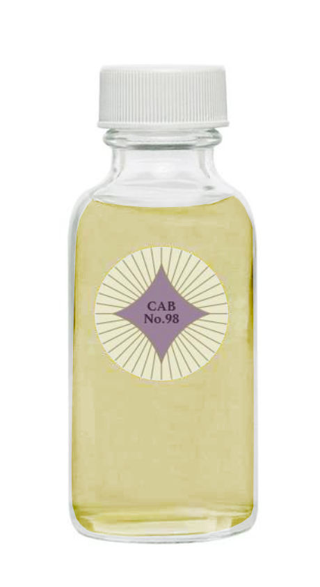 Container of Cabernet No. 98 potpourri refresher oil.  Glass bottle has a white cap and a round circular label.  The table has a purple 4 point star with rays radiating from it.