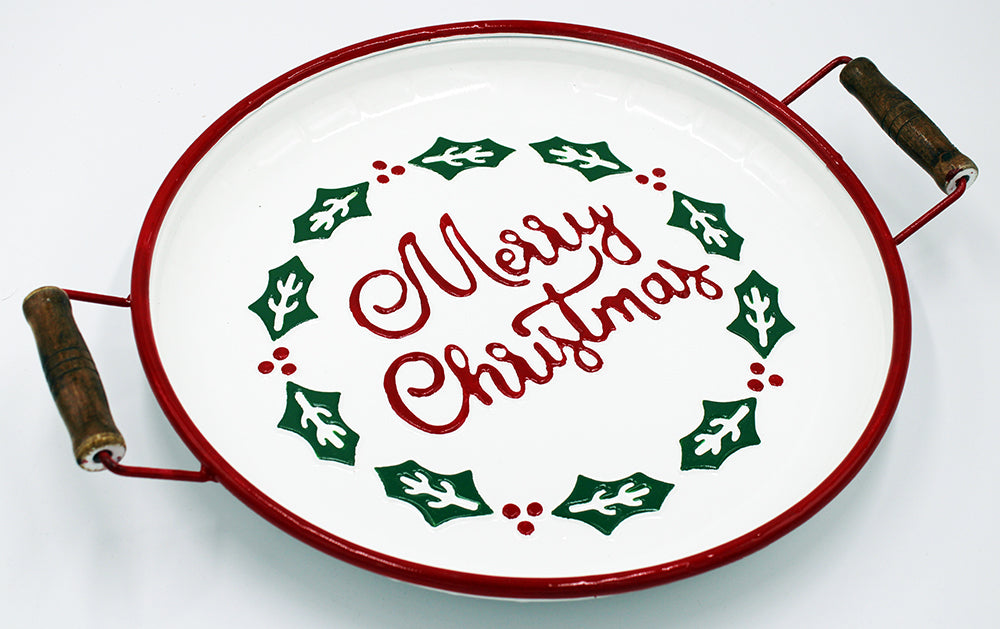 White enamel tray with red trim.  Merry Christmas is written in the middle and is surrounded by a border of holly and berries.  The tray also has wooden handles on either side.