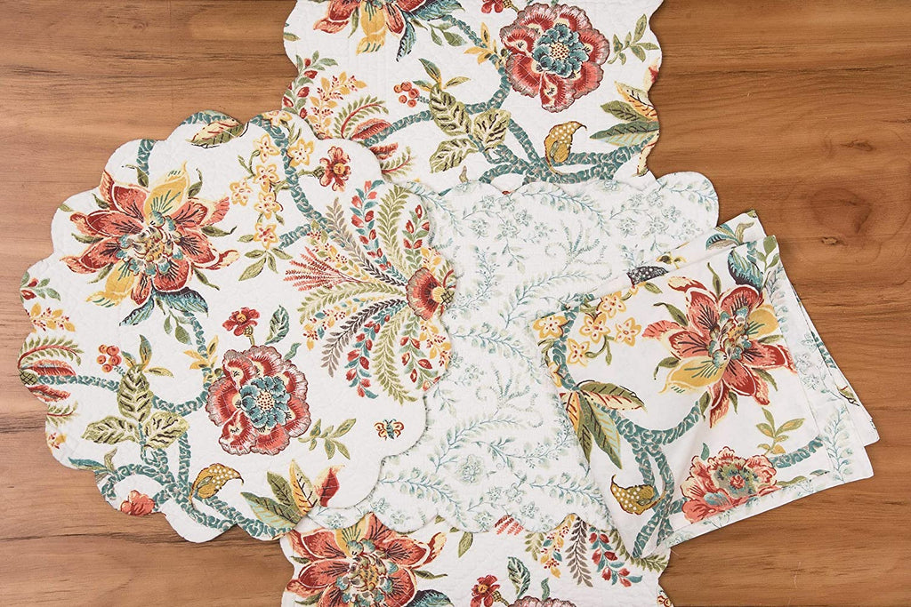 A collection of place setting textiles on a wooden surface.  Each item has the same multicolor floral pattern, featuring reds oranges yellows and jewel tone blues and greens on a white background.  Featured here are a round placemat with scalloped edges, a runner, and napkins.