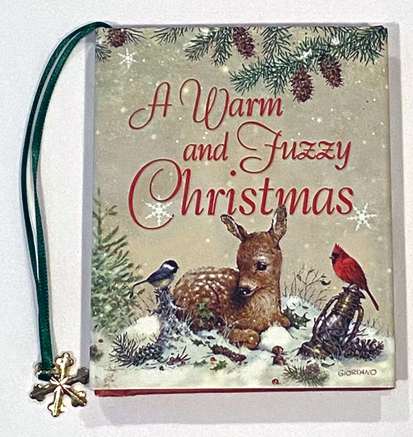 Photo of the cover of the book 'A Warm and Fuzzy Christmas' - showcasing a deer laying in snow with a finch and a cardinal looking at it.  The book features a green ribbon bookmark with a 6 point gold plated snowflake.