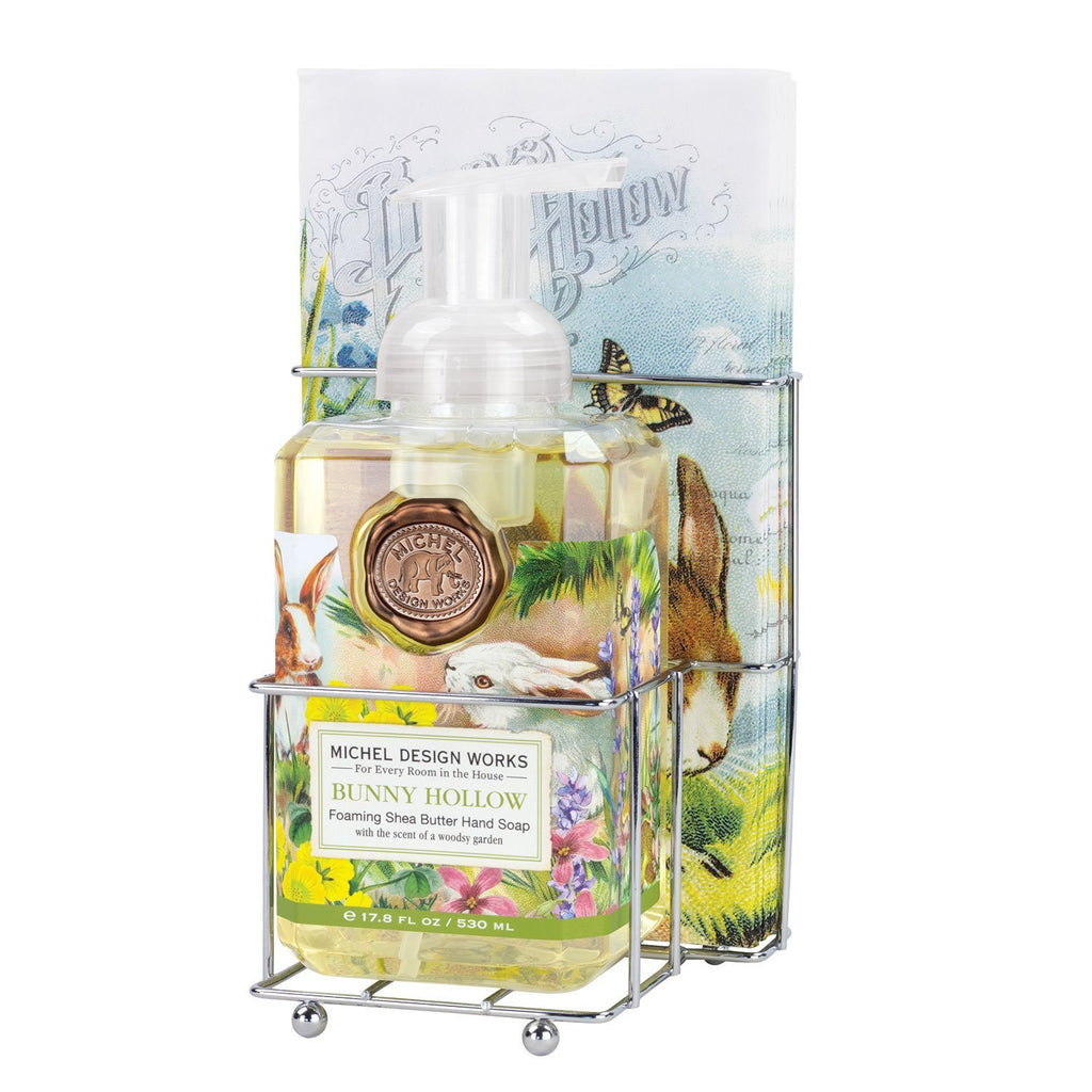 A chrome caddy with coordinating napkins and foaming hand soap.  Images on the label and napkins are of bunnies frolicking in a hollow around spring flowers.