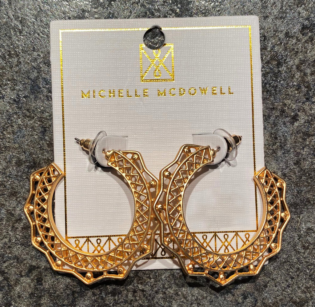 A pair of ornate gold hoops on a display card from Michelle McDowell.