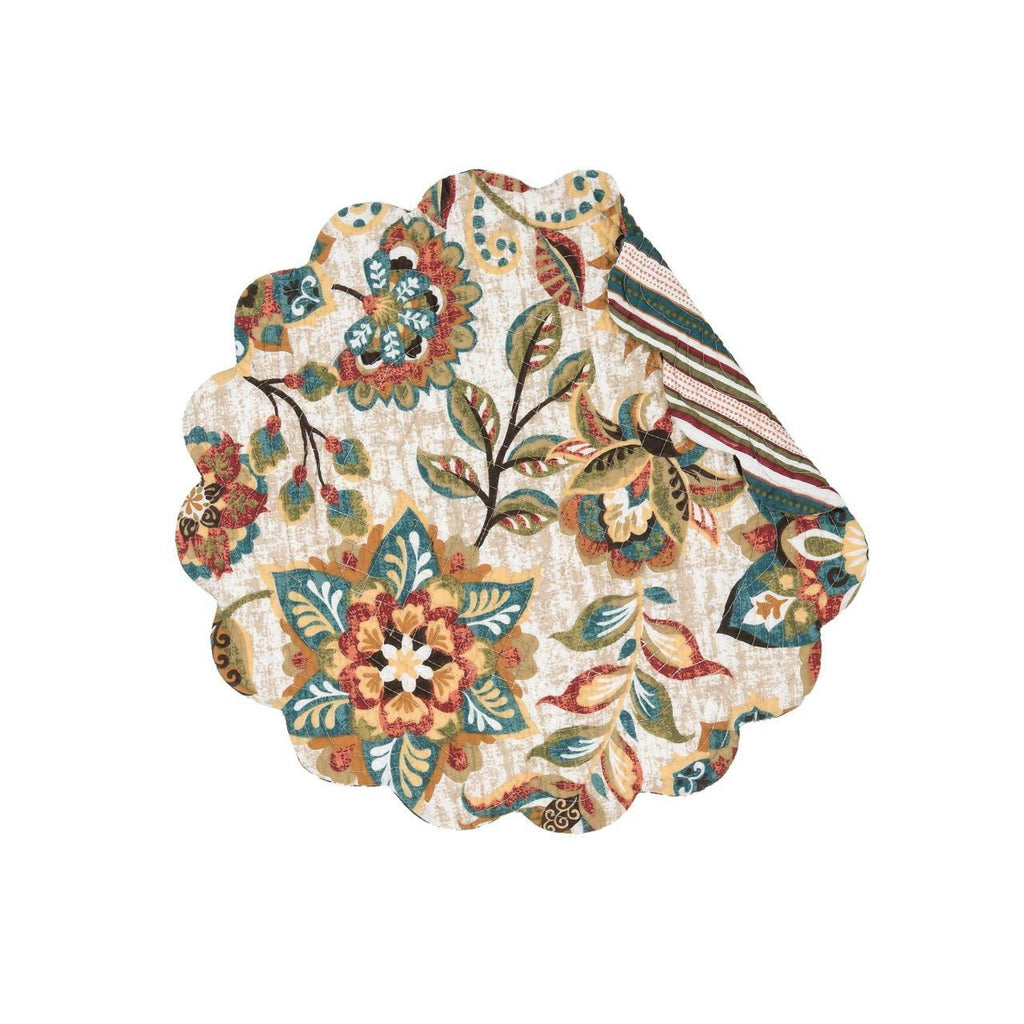 A round scalloped quilted placemat on a white background.  The pattern is of flowers and leaves in hues of ochre, tomato, blue, green and brown.  A corner is folded over showing a striped pattern in the same colors as the front.