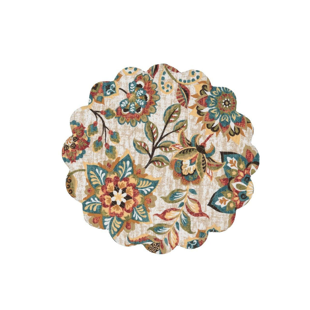 A round scalloped quilted placemat on a white background.  The pattern is of flowers and leaves in hues of ochre, tomato, blue, green and brown.