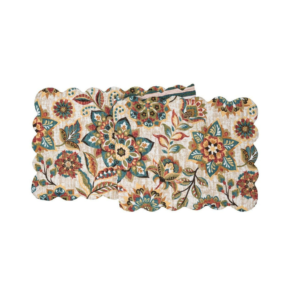 A rectangular scalloped quilted runner on a white background.  The pattern is of flowers and leaves in hues of ochre, tomato, blue, green and brown.