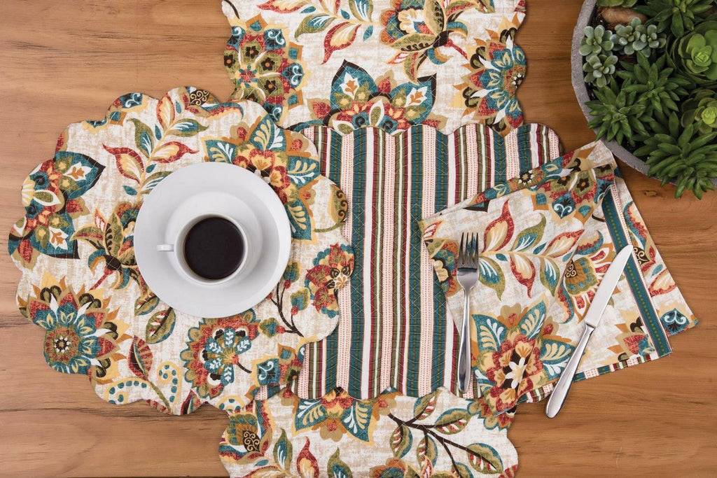 A collection of place setting textiles on a wooden background.  Each item has the same multi colored floral pattern of sage blue brown tomato and ochre.  A round scalloped placemat sits on top of a runner and a coordinating square napkin is to the right.