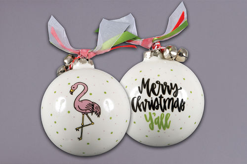 White glass ornament with a flamingo on one side and the text 'Merry Christmas Y'all' on the back.  Green dots feature all over the ornament.  Decorating the top of the ornament are red, white and green ribbon, and a set of jingle bells.