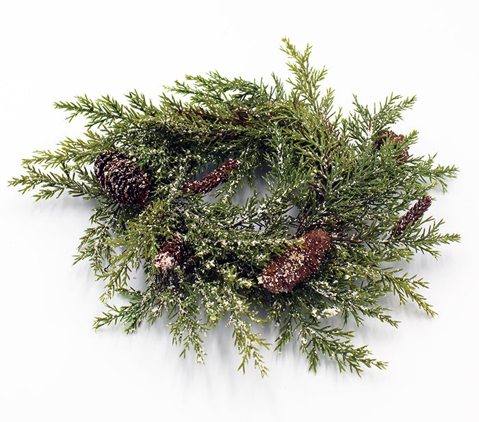 Lightly flocked evergreen candle ring with a variety of pine cones attached.