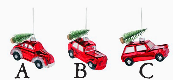 Three different glass ornament red vehicles, each with a small bottle brush Christmas Tree on top.  The car on the left looks similar to a VW bug.  The car in the middle is similar to a sedan from the 50s.  The car on the right is a hatchback.