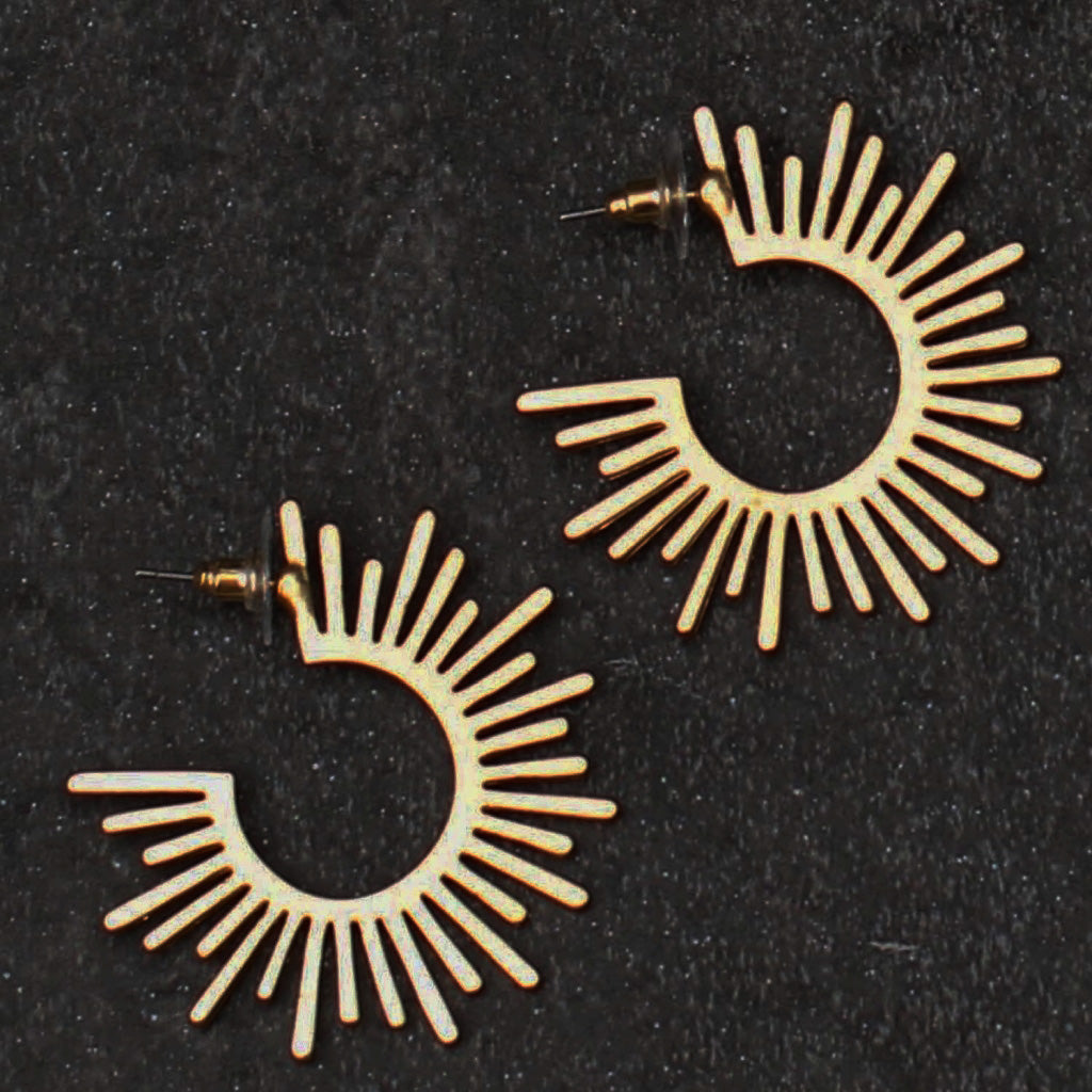 A pair of earrings on a black sandy surface.  The earrings are shown in side profile, and are 3/4 of a complete hoop.  Various lengths of material radiate from the open center, reminiscent of a paint splatter or sun rays.