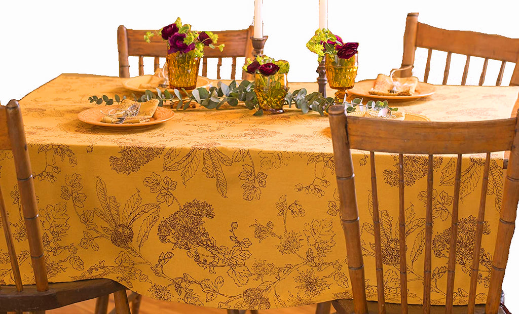 Table set for four with amber glasses with flowers in them, candlesticks and yellow plates.  A sprig of eucalyptus is in the center of the table.  The table cloth has a gold background and burgundy line work of fall leaves and flowers.