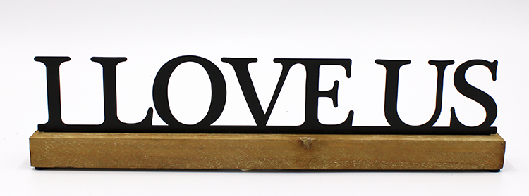 Metal text sign that states 'I Love Us' in black letters with serif.  Letters are attached to a wooden board below.  Sign is in front of a white background.