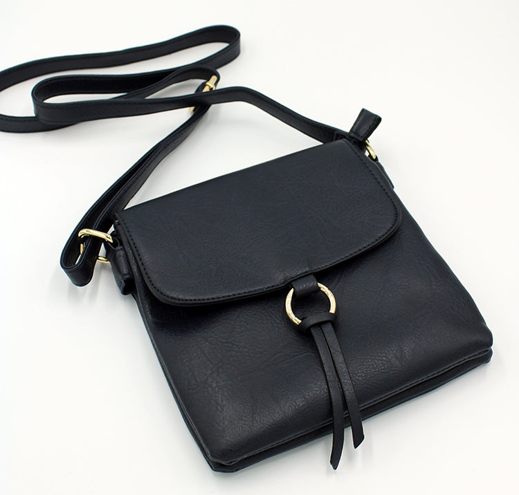Black square purse with long strap and flap.  Flap has a round brass circular detail with a leather tassel tied to it.