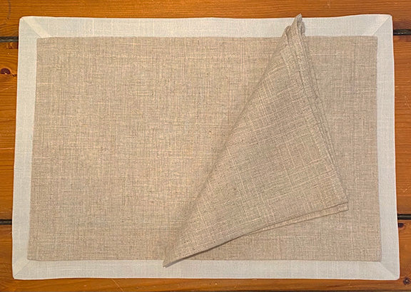 Linen napkin and placemat on a wooden table.  Placemat has a cream border around the natural linen center.