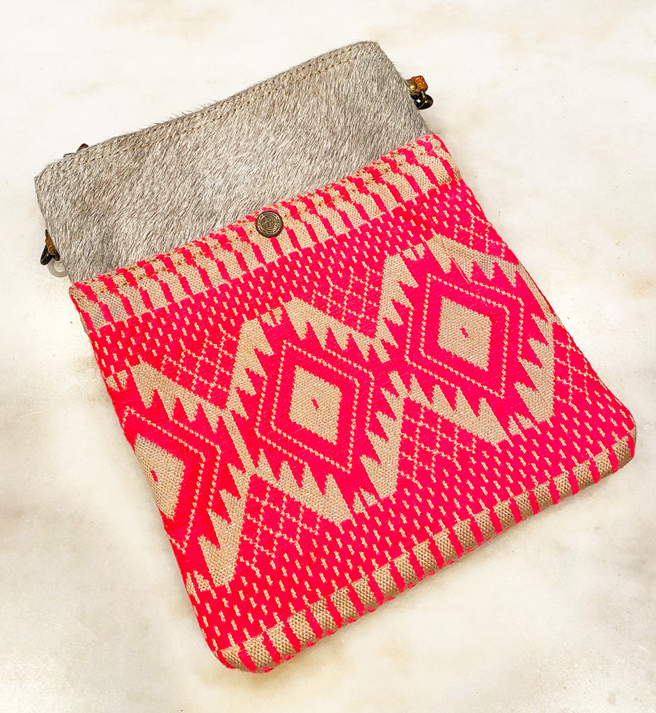 A photo of a crossbody bag with a woven hot pink pattern and a gray fur trim at the top.