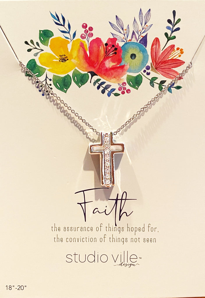 An image of a silver chain necklace with three silver pendants on it, on a card with art of flowers and text that reads 'Faith the assurance of things hoped for, the conviction of things not seen. Studioville design.'  The three silver pendants on the chain form a Catholic cross when they are together, with a vertical row of cubic zirconias in the middle.