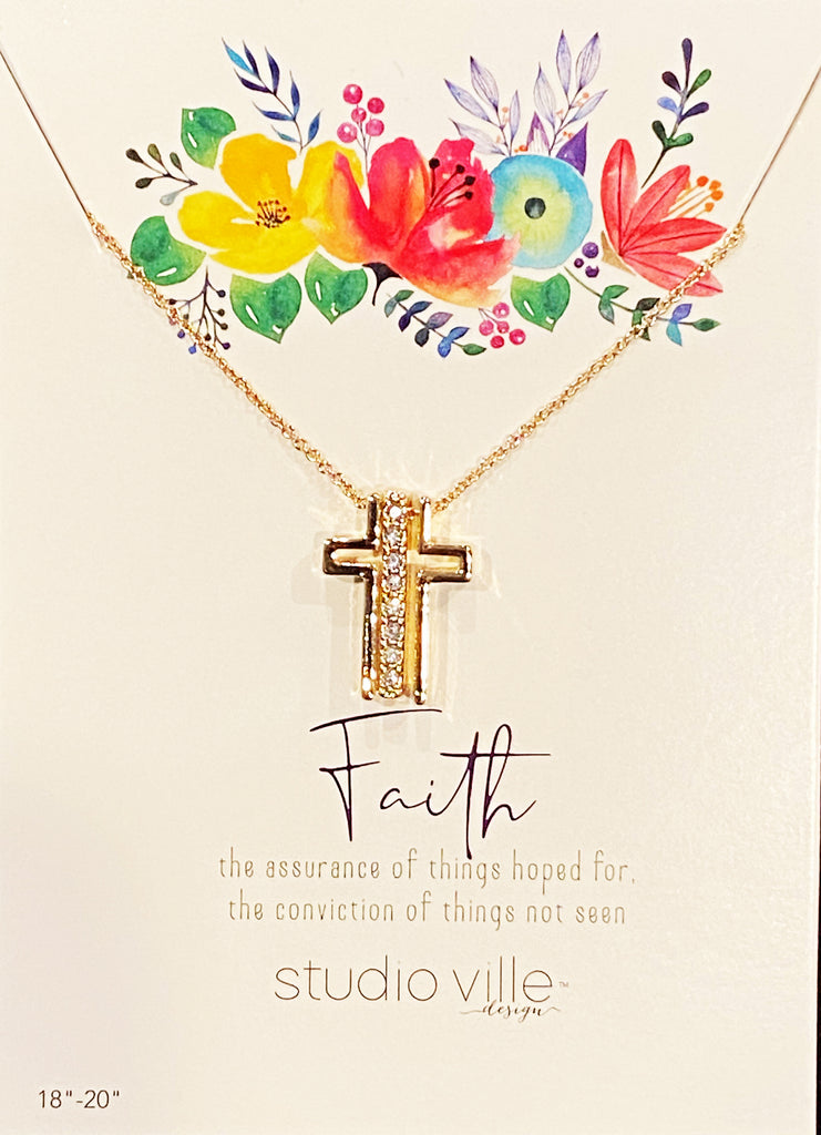 An image of a gold chain necklace with three pendants on it, on a card with art of flowers and text that reads 'Faith the assurance of things hoped for, the conviction of things not seen. Studioville design.'  The three gold pendants on the chain form a Catholic cross when they are together, with a vertical row of cubic zirconias in the middle.