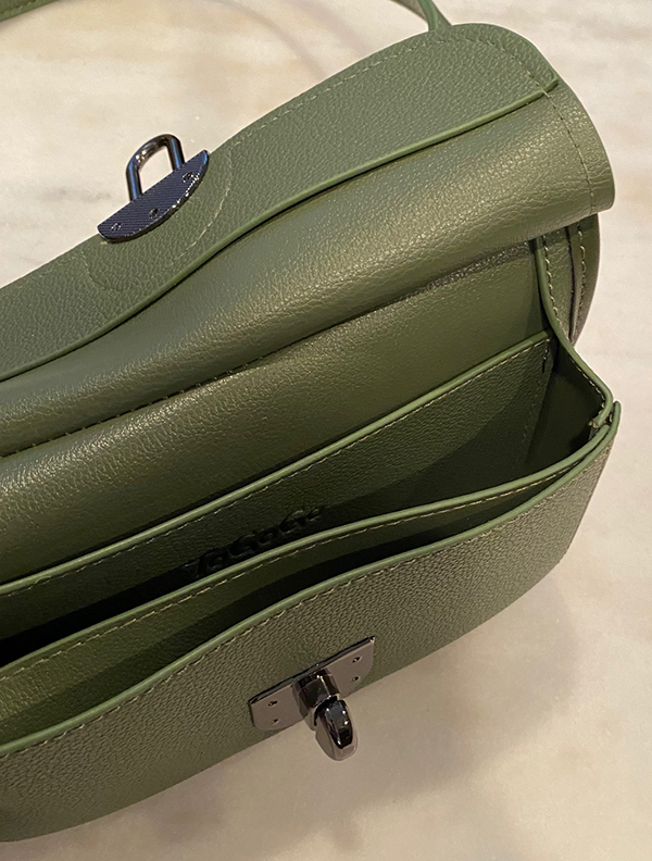 Inside of olive green purse on a marble surface.