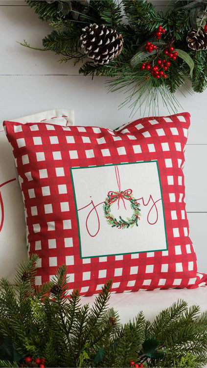 Square pillow with red gingham pattern and a beige square in the middle that says 'joy'.  Joy features a wreath in place of the o.  Evergreen garlands are above and below the pillow in front of a white wooden background.