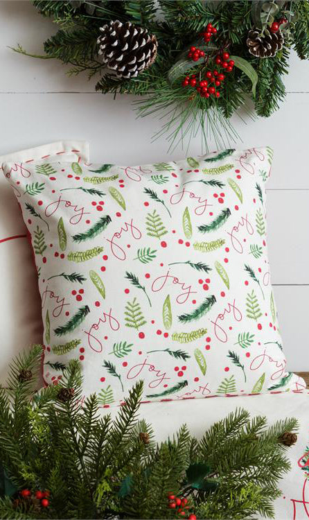 Square pillow with a variety of artistic representations of holiday greenery, red berries, and the text joy, in a random pattern.  Evergreen garlands are above and below the pillow in front of a white wooden background.