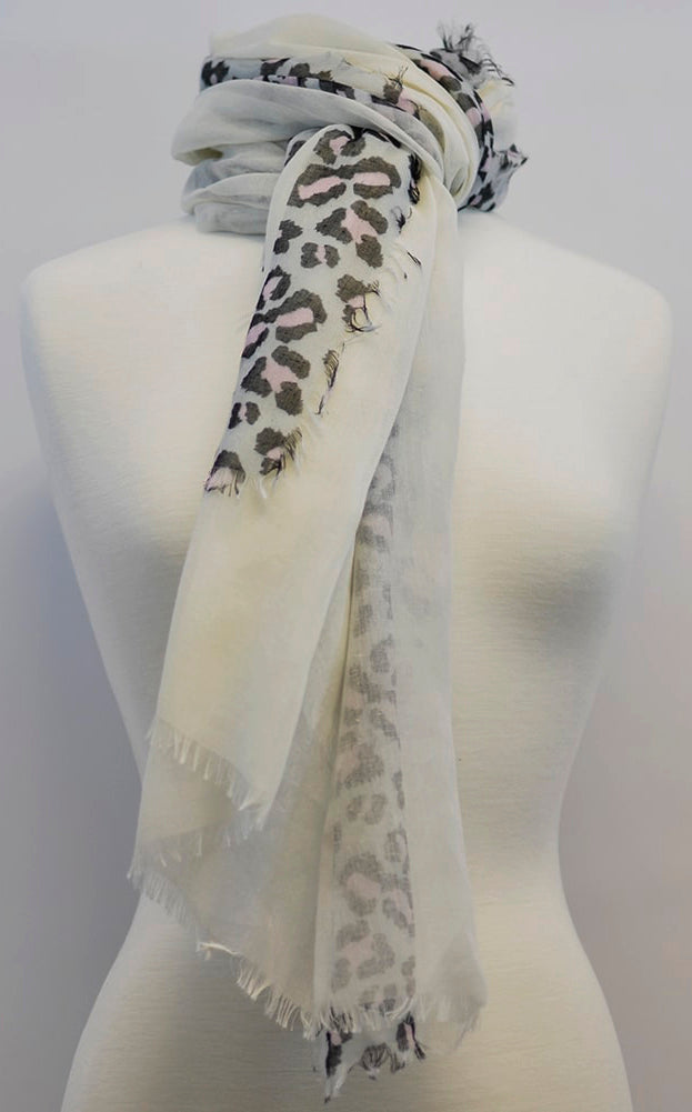 White scarf with black and pastel pink leopard spots wrapped around the neck of a mannequin
