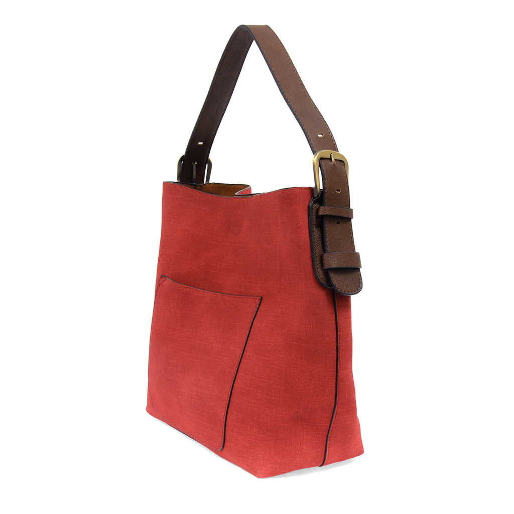 Red faux linen hobo bag with brown buckle strap, and accompanying brown insert bag with cross body strap.